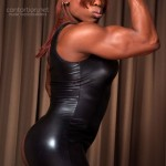 Nude female bodybuilder poses in tight-fitting spandex suit