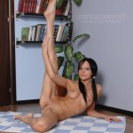 Naked gymnast is posing before the cam on yoga carpet